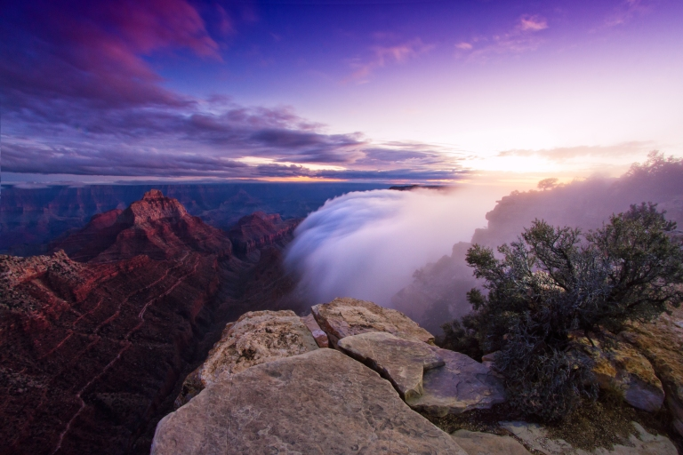 Clouds flow over cliff walls on the north rim of the Grand Canyon.